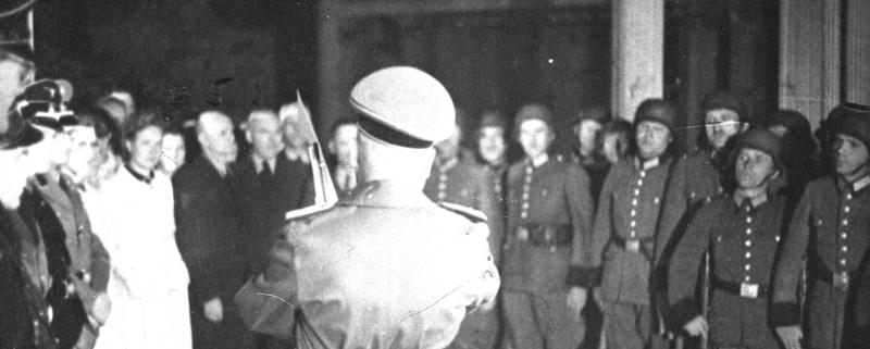 Gestapo-Kommissar Michael Völkl bei der Befehlsausgabe an Wachen und Kontrolleure im Platzschen Garten